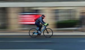 Fast motion photograph of man on bike in city centre